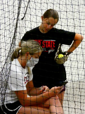 Shelby McCombs reviews videos of Reese Wells, 12, pitching form during a training session at McCombs Elite Fastpitch in Newark. McCombs played softball at Licking Valley and in college for Ohio State University.