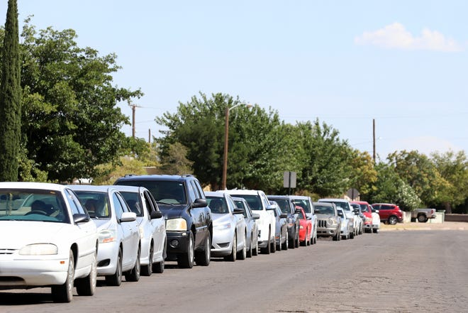 Vehicles circle the entire block to receive fruit and vegetable boxes at the Deming National Guard Armory.