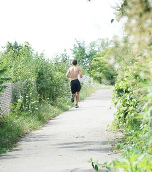 A jogger uses the I-275 trail just east of Haggerty south of Nine Mile on July 30, 2020.