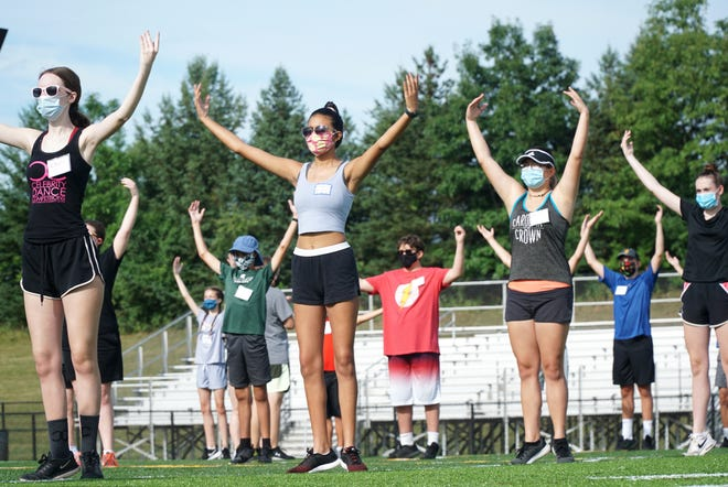 Plymouth-Canton Community Schools marching band members work on their choreography at the school's track on July 30, 2020.