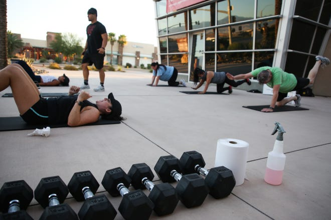 Ryann McMillon, owner of Fit in 42, coaches students during an outdoor workout class on Thursday, July 30, 2020, in Palm Springs, Calif. Gov. Gavin Newsom closed salons and gyms, only permitting outdoor operations on July 13 in an effort to slow the spread of COVID-19.