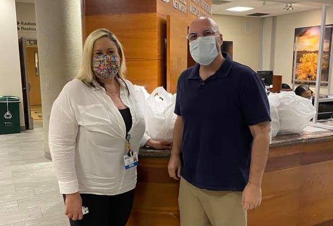 Erin Teran and Christopher Itai Cardona are photographed at Desert Regional Medical Center with 75 donated meals behind them.