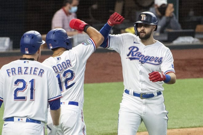 Joey Gallo, de los Rangers de Texas, es felicitado por el venezolano Rougned Odor y por Todd Frazier, luego de conectar un jonrón de dos carreras ante los Diamondbacks.