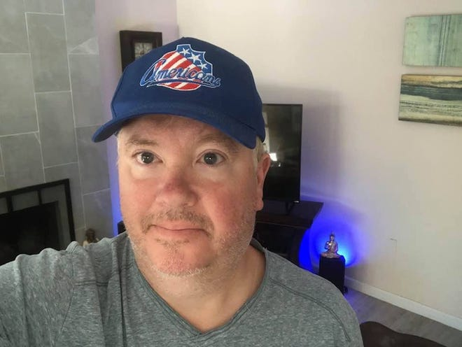 Rochester native Mike Baldwin at home in Sacramento, California, in his Rochester Americans-branded baseball cap.