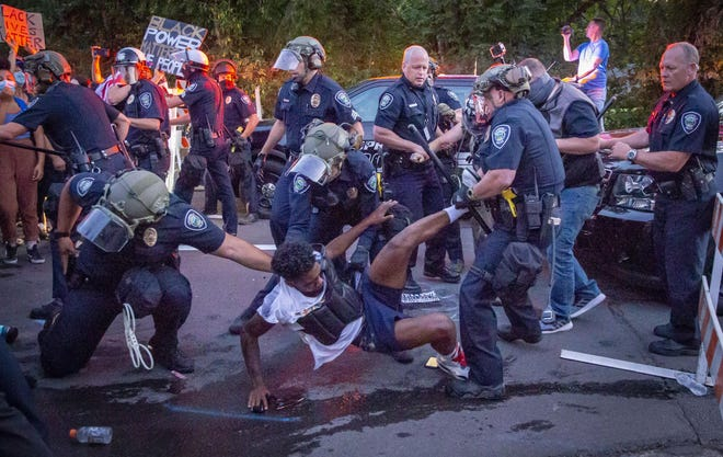 Black Unity's Tyshawn Ford is dragged away by Springfield Police Wednesday night at a barricade erected at 67th Street and Dogwood by police during the Thurston protest.