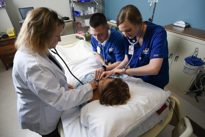 ASU nursing students practice with their instructor in the High-Fidelity Simulation Lab