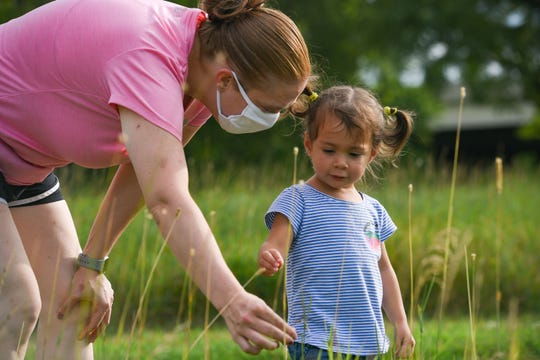 Mollie Sanchez helps her daughter, Zoie (2), look at a plant while taking a detour on their walk on Wednesday, July 29, at Yankton Trail Park in Sioux Falls.