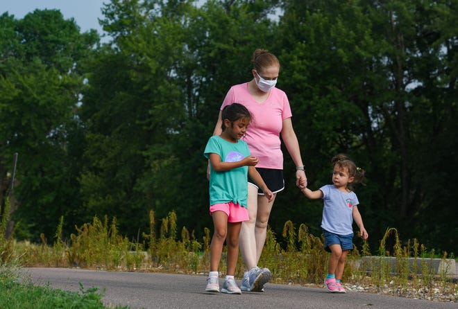 Mollie Sanchez goes for a walk with her daughters, Liliana (6) and Zoie (2) on Wednesday, July 29, at Yankton Trail Park in Sioux Falls. Sanchez won the mayor's fitness challenge to bike, walk or run 100 miles in 100 days.