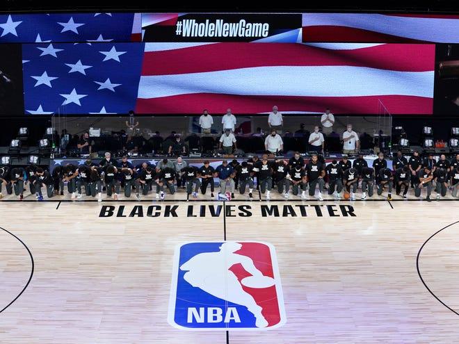 The Pelicans and Jazz kneel before the NBA's restart opener in Orlando.