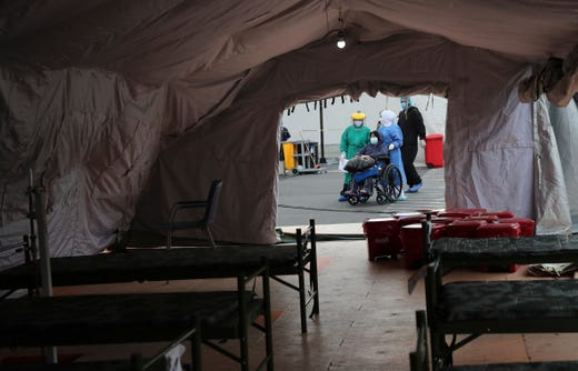 A person who tested positive for the new coronavirus is transferred to one of the tents set up outside the Seguro Social hospital to continue their treatment, in Quito, Ecuador, Wednesday, July 29, 2020. The Ecuadorian capital has experienced a surge in COVID-19 cases since the government started to reopen the economy last month.