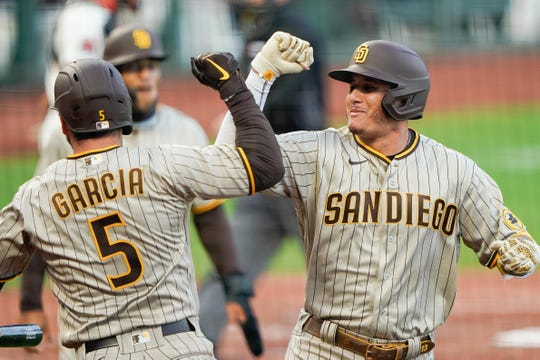 San Diego Padres third baseman Manny Machado (13) celebrates with second baseman Greg Garcia (5) after hitting a two-run home run against the San Francisco Giants during the third inning at Oracle Park on July 29.