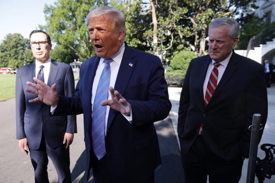 President Donald Trump speaks as Treasury Secretary Steven Mnuchin and White House Chief of Staff Mark Meadows listen prior to Trump's Marine One departure from the South Lawn of the White House on Wednesday.