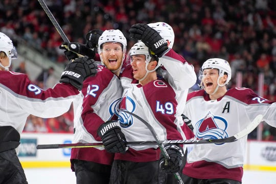 Colorado Avalanche defenseman Samuel Girard (49) celebrates with teammates, including Gabriel Landeskog (92) and Nathan MacKinnon (29), after scoring a goal during a February game against the Carolina Hurricanes.