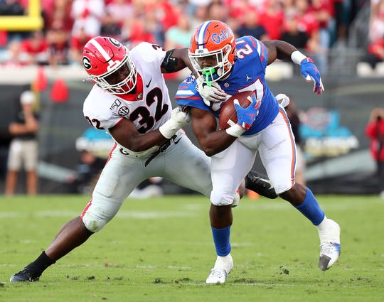 Florida running back Dameon Pierce is grabbed by Georgia linebacker Monty Rice during the second half of their 2019 game at TIAA Bank Field in Jacksonville, Florida.