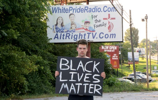 Rob Bliss, holds a Black Lives Matter sign in Harrison, Arkansas. Bliss posted a video of the reactions he received to the sign.