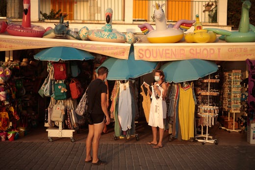 A woman shops for dresses in town of Sóller in the Balearic Island of Mallorca, Spain, Wednesday, July 29, 2020. Concerns over a new wave of coronavirus infections brought on by returning vacationers are wreaking havoc across Spain's tourism industry, particularly in the Balearic Islands following Britain's effective ban on travel to the country.