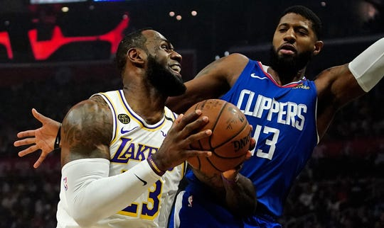 LeBron James controls the ball as the Clippers' Paul George defends during game on March 8.
