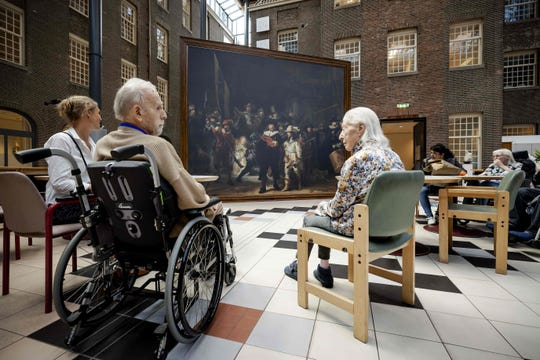 Residents of the Dr. Sarphati House nursing home in Amsterdam, The Netherlands, sit in front of a same size version of the famous painting 'The Night Watch' by Dutch painter Rembrandt van Rijn, in Amsterdam on July 20, 2020. - This summer, the Rijksmuseum brings a version of the world-famous painting by Rembrandt to thirty nursing and care homes and senior complexes. Outings to cultural institutions are not possible for many elderly people due to the coronavirus crisis.