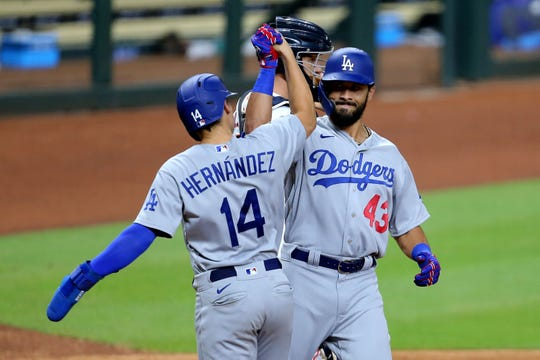 Los Angeles Dodgers third baseman Edwin Rios celebrates his 13th-inning homer against the Houston Astros with Enrique Hernandez.