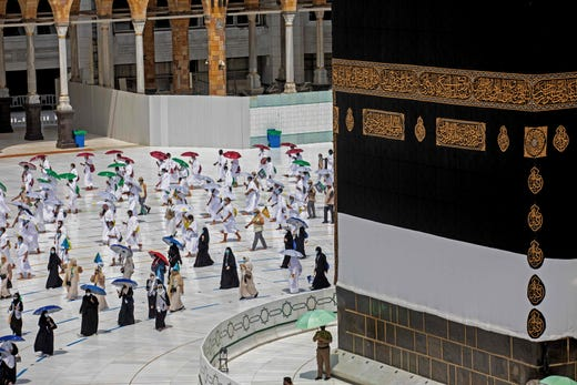 A handout picture released by the Saudi ministry of media shows a small number of pilgrims circumambulating around the Kaaba, Islam's holiest shrine, at the center of the Grand Mosque in the holy city of Mecca in Saudi Arabia at the start of the annual Muslim Hajj pilgrimage on July 29, 2020.