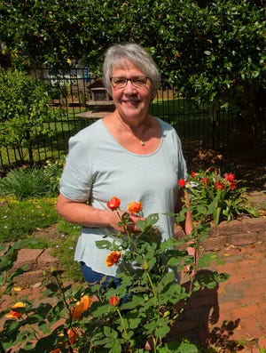 Julie Meyer stands among some flowers in her multiple gardens at her home.