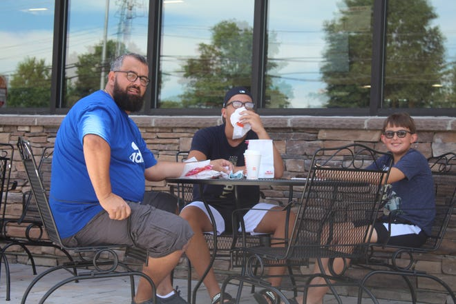 Customers Eugen Zhegra, Enea Sinani and Eric Zhegra enjoy the outside seating at the new Dunkin' location, 1128 Forrest Ave.