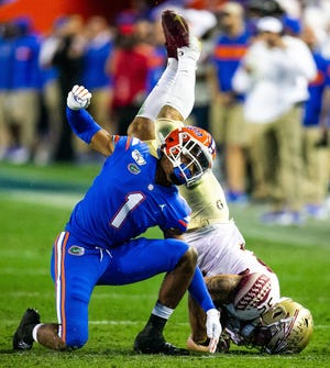 Jaguars cornerback CJ Henderson celebrates a tackle of Florida State receiver Gabe Nabers in last year's game in Gainesville. Henderson is expected to start in week one of the NFL season.