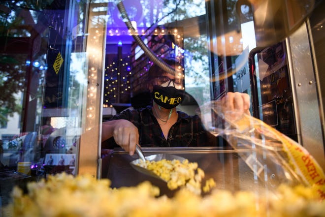 Elizabeth Crumbler scoops up some popcorn for a customer's order at the Cameo Art House Theatre on Friday, July 31, 2020. The theater, which has been closed since March, is selling concessions curbside.
