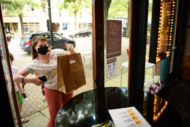 Ashley Tucker picks up her order of movie snacks at the Cameo Art House Theatre last Friday. The theater, which has been closed since March, is selling concessions curbside.
