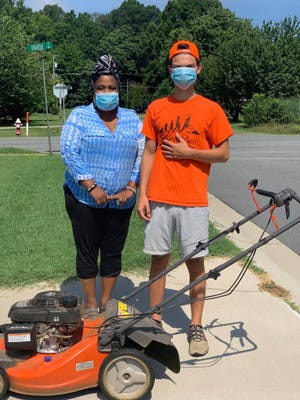 Adrienne Griffin-Frazier stands next to Richard Hurst, who mowed her yard for free. This was Richard's final yard before completing the 50-yard challenge, but he plans to continue mowing for free to help those who need it in his community.