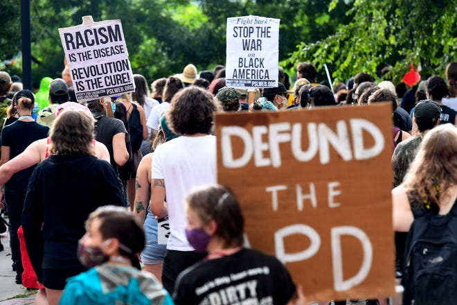 People marched in the streets of Asheville to protest the annual budget that was passed in a 5-2 vote July 30. The budget allocates three months of funding for the Asheville Police Department and most other city functions.