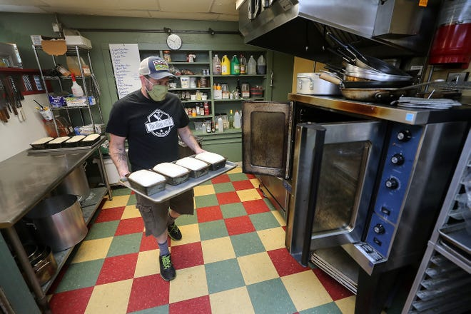 Ben White, co-owner of The Shop at 2712, moves loaves of homemade sourdough bread to the oven at the restaurant in Bremerton on Friday. White teamed with the owner of another food truck to open the restaurant, which offers takeout only.