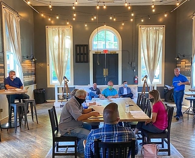 Kirby Hasseman, far right, speaks at the first meeting of the 3 for 3 Coshocton County Initiative at the Township Room in Roscoe Village. Community leaders met to discuss the drive and it's launch.