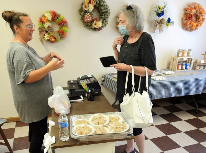 Lori Parrish checks out Angela DePalma at Lori's Hilltop Market. In addition to fresh produce from her garden, Lori offers a variety of items sucah as baked goods, candles and wreaths which she makes. The market has been open nearly a month.