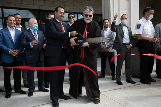 Chairman of the board of directors for The Chaldean Community Foundation Sylvester Sandiha held an oversized pair of scissors with Bishop Francis Kalabat as the foundation held a ribbon cutting Friday July, 31, 2020 revealing their new renovations and expansion of their Sterling Heights location.