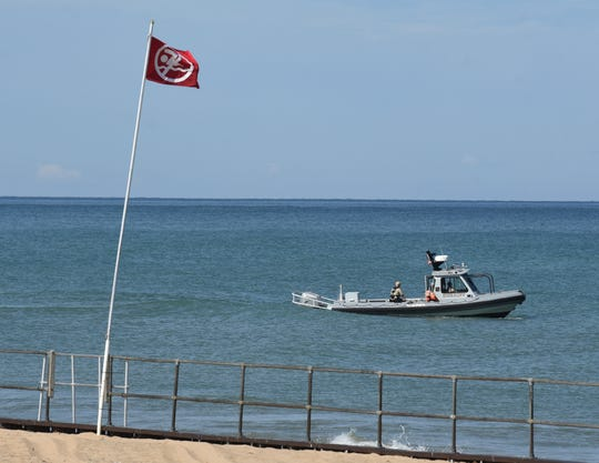 A Berrien County Sheriff Department Marine division boat motors off the beaches at Warren Dunes State Park, in Bridgman, Mich., Friday, July 31, 2020, as rescue crews search for a missing swimmer.