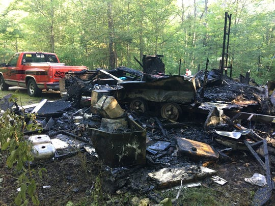 Officials said the man held up the camper's roof to enable his wife and dog to escape the fire.