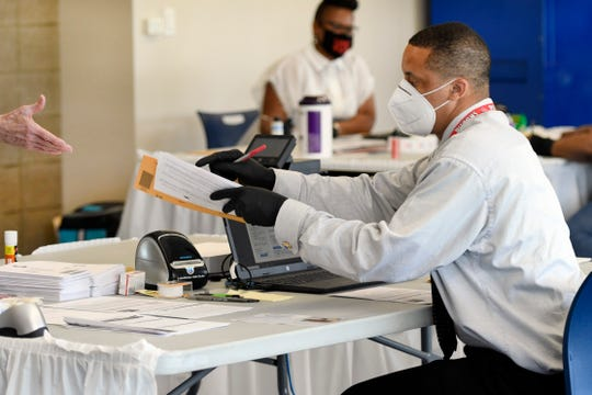 An election worker hands an absentee ballot to a voter at a satellite voting location on the campus of Wayne County Community College NW district, Friday, July 31, 2020, in Detroit.