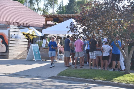 Patrons wait outside The Little Fleet, a collection of food trucks in Traverse City on Thursday, July 30, 2020. The interior bar and seating will be closed at midnight at the Traverse City restaurant.