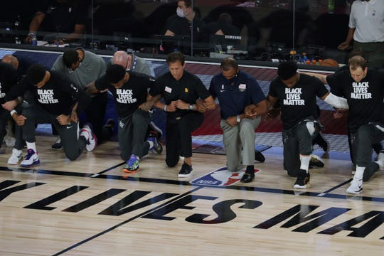 Players and coaches kneel during the national anthem before the Utah Jazz against the New Orleans Pelicans NBA basketball game Thursday, July 30, 2020, in Lake Buena Vista, Fla.