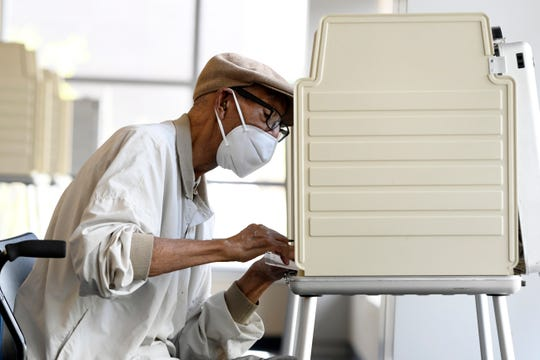 Virgil Anderson of Detroit fills out his absentee ballot at a satellite voting location on the campus of Wayne County Community College NW district, Friday, July 31, 2020, in Detroit.