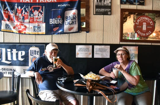 Roger and Carol Bauer of Traverse City enjoy cocktails and beer at The Union Street Station on Thursday, July 30, 2020. the doors will close at the Traverse City restaurant on midnight unitl the Governor's orders are lifted.