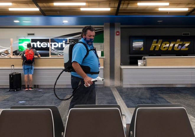 EVV airport custodian Andy Ellis sanitizes surfaces with an electrostatic sprayer in efforts to combat the spread of COVID-19 at the Evansville Regional Airport Friday morning, July 31, 2020.
