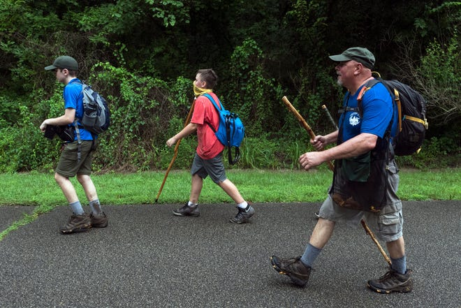 "Assistant Scoutmaster Ricky Lockard, right encourages Boy Scouts with Troop 305 and 315 as they head back to camp singing ""99 bottles of milk on the wall"" on their hike Thursday afternoon, July 30, 2020. The Newburgh scouts usually spend a week at Camp Ransburg on Lake Monroe but due to coronavirus cancellations, they battled the elements closer to home in Harmonie State Park."