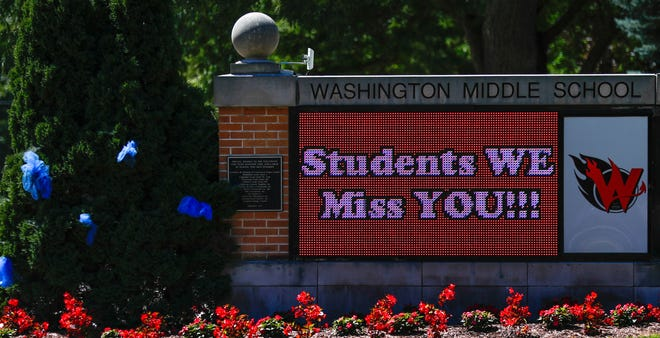 A sign at Washington Middle School in Green Bay displays 'Students WE miss YOU!!!' on Friday.