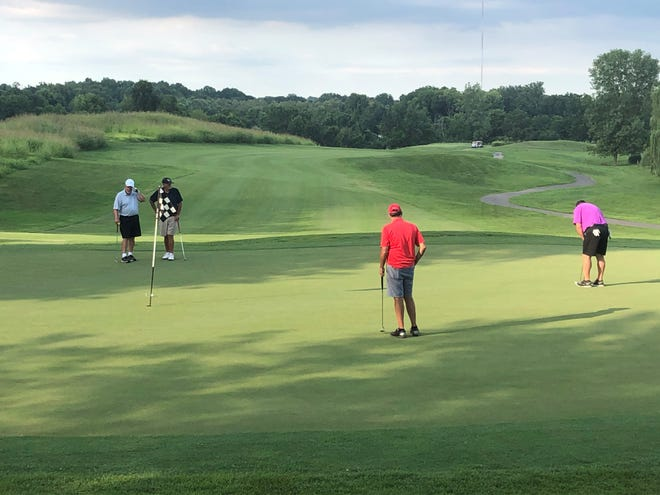 The group of Mike Wright, Taylor Sparks and Mike McGill, from left, watch Al Starnes putt on the 18th green Tuesday at the Bridges Golf Course of Henderson. The group of men, who all live in Cadiz, Kentucky, has a goal of playing every golf course in Kentucky to raise money for Relay for Life.
