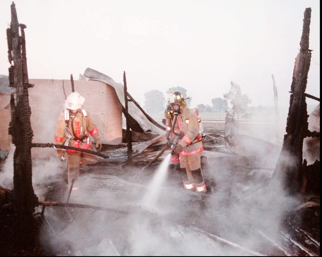 Firefighters spray down the remains of Barn 11 at Ellis Park racetrack July 31, 1995, after 27  horses were killed in an accidental blaze. It was the second worst fire in the track's history. A fire Aug. 23, 1978, which killed 31 horses, was determined to be arson. (Dan Kern photo for the Evansville Press)