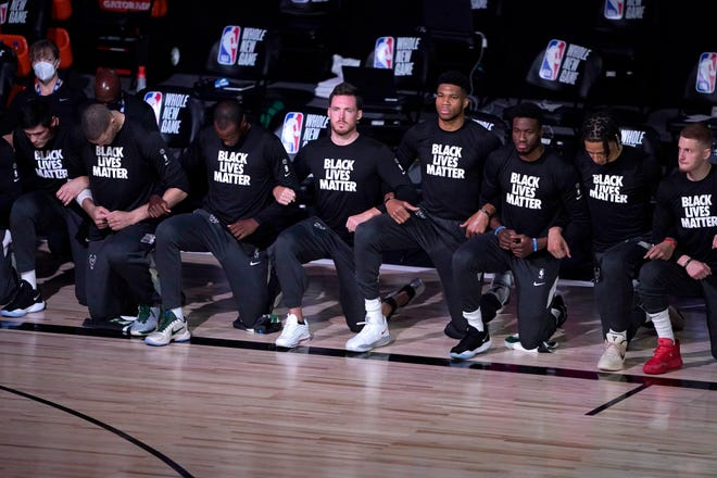 Players kneel and wear Black Lives Matter shirts before the start of the Bucks-Celtics game Friday.