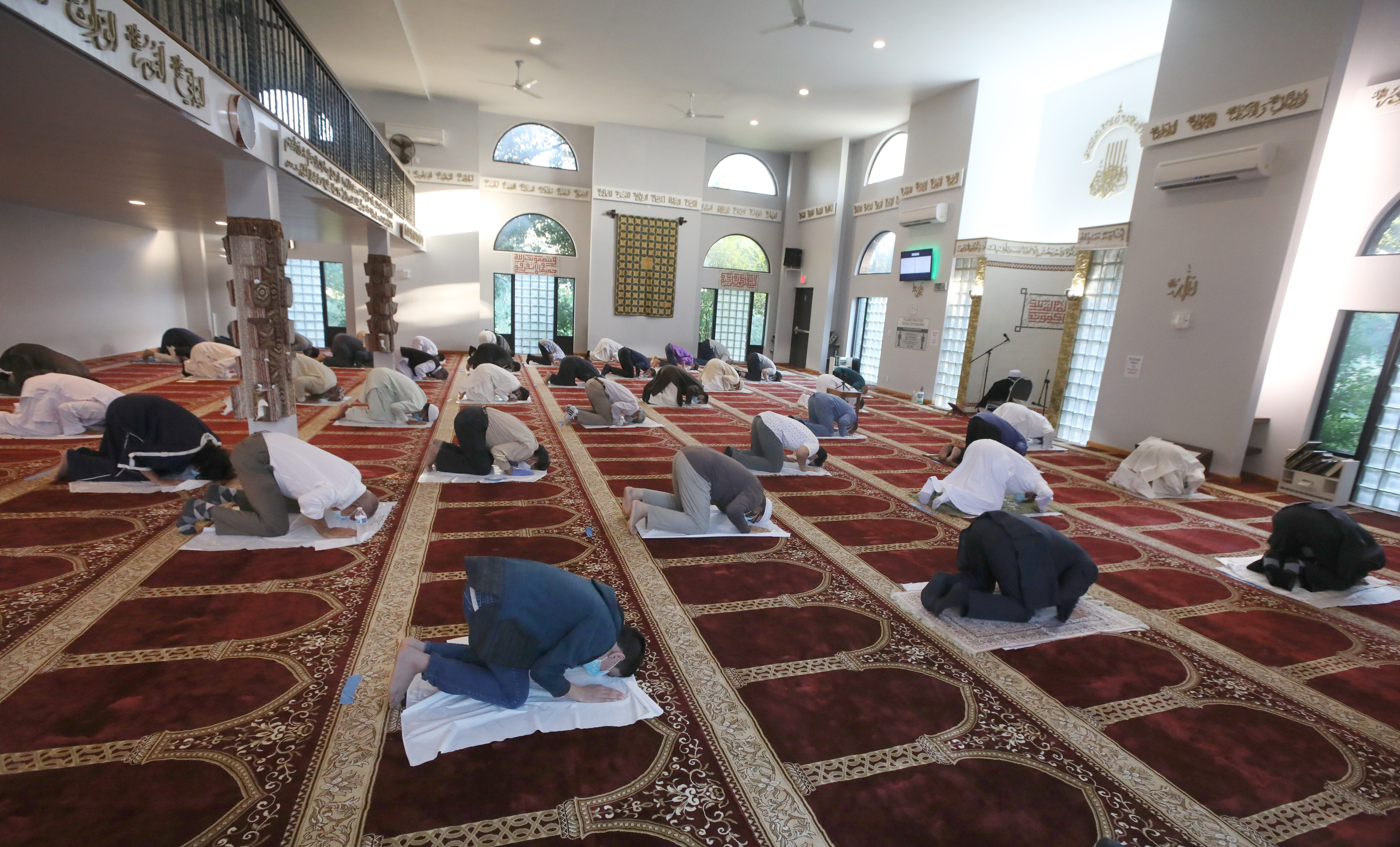 Inside the Islamic Center of Rochester, Rochester-area Muslims pray as they celebrate Eid al-Adha July 31, 2020. Due to coronavirus, the Center took extra precautions, setting up plastic sheets spaced six feet apart all throughout inside the prayer hall.