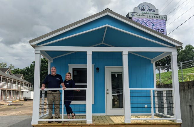 Bryan and Amy Stallings, founders of Elevate Branson, stand on the front porch of a model tiny home that will be available for tours for the next 60 days.